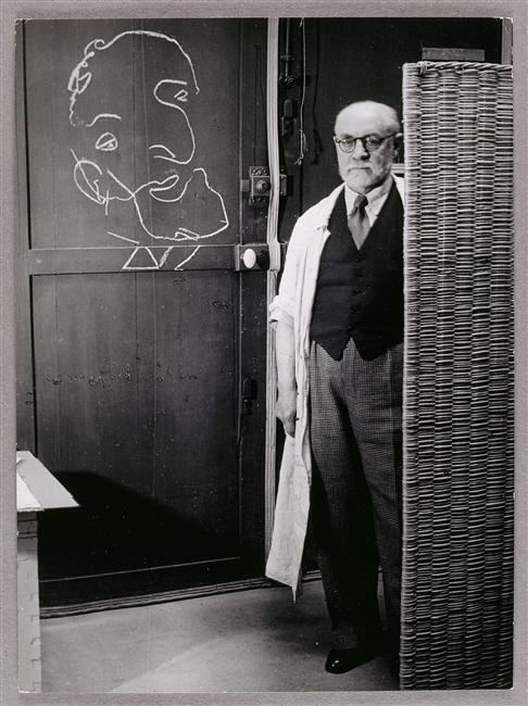 Henri Matisse standing against a screen and drawing with chalk, 1939